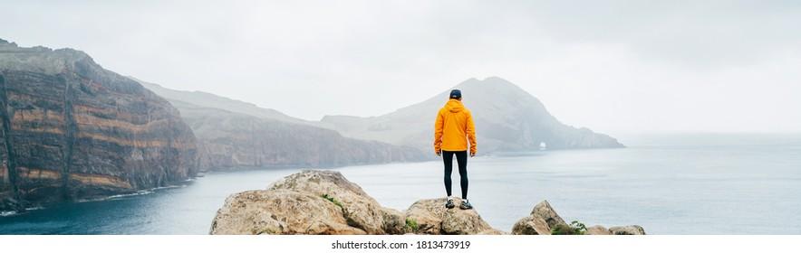 Trail runner man dressed orange waterproof jacket, running tights and shoes enjoying Atlantic ocean bay view on Ponta de Sao Lourenço peninsula -the easternmost point of Madeira island, Portugal