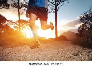 trail runner man exercising for fitness at sunrise in mountains doing sport