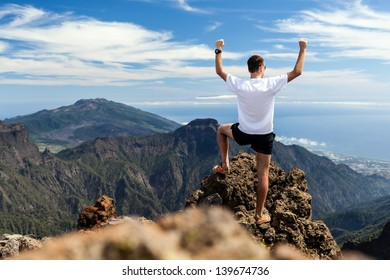 Trail runner, man and success in mountains, arms raised. Running, sports, fitness and healthy lifestyle outdoors in summer nature