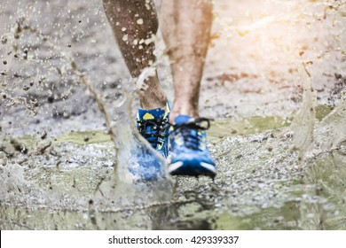 Trail runner man walking in a puddle, splashing his shoes. Cross country trail