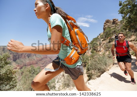 0193844b Trail runner woman in cross country running race in Grand Canyon. Couple  training working out