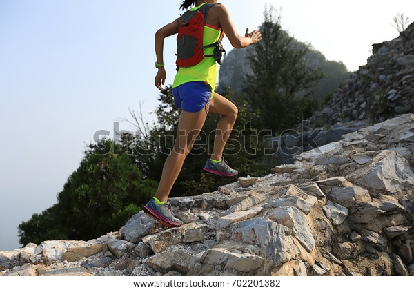 trail runner woman running at great wall on the top of mountain