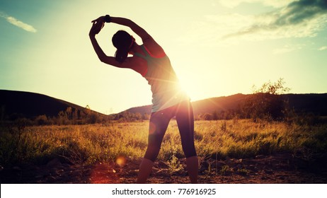 trail runner woman stretching arms before run on sunset forest