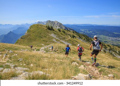 Trail runners running in the mountain in a sunny day