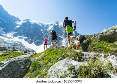 Trail runners running and training in the hills and mountains of the Alps in Europe, running towards a steep and snowy mountain along a trail in summer