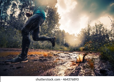 Trail running athlete crossing the dirty puddle in the forest