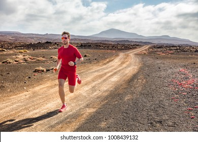 Trail running athlete fitness man runner sprinting on desert dirt road wearing compression clothes and wearable tech smartwatch watch for cardio tracking. Summer outdoor landscape.