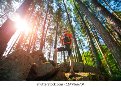 Trail running athlete having a rest and drinking the water from hydration pack being in the forest with rocks