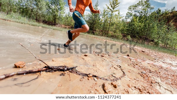 Trail running athlete moving through water and mud on rural road