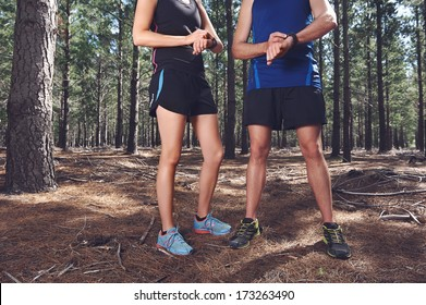 Trail running couple check time on their gps watch for tracking pace