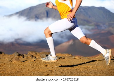 Trail running - male runner in cross country run. Closeup of strong legs and running shoes sprinting at speed. Male athlete fitness runner in compression sports clothing, socks and shorts.