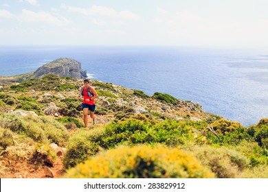 Trail running man cross country running in mountains on summer beautiful day Training and working out fitness healthy colorful runner jogging and exercising outdoors on rocky footpath on Crete, Greece