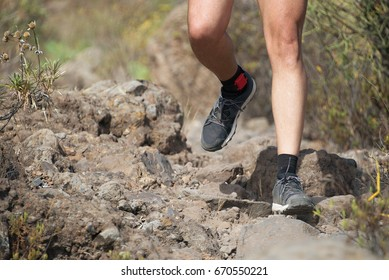 Trail running man on mountain path exercising,workout outdoors on rocky terrain
