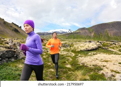 Trail running people in cross country run. Woman and man runners training jogging outdoors in beautiful mountain nature landscape on Snaefellsnes, Iceland.