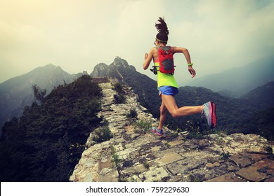 trail running woman at great wall on the top of mountain