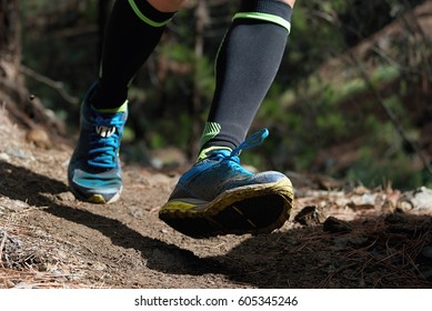Trail running workout outdoors on rocky terrain, sports shoes detail on a challenging forest track