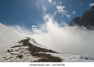 Trail in snowy mountains in the background fog on a sunny day