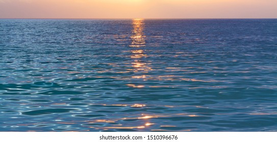 A trail of sparkling, golden light from the setting sun and light patterns on the ocean. A band of orange sky on the horizon.