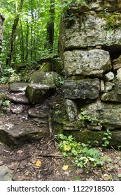 A trail through an abandoned stone building in a forest.  Old Stone Fort State Archaeological Park, Manchester, TN, USA.