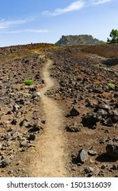 Trail through rough volcano landscape on top of the Cumbre Vieja in La Palma, Spain.