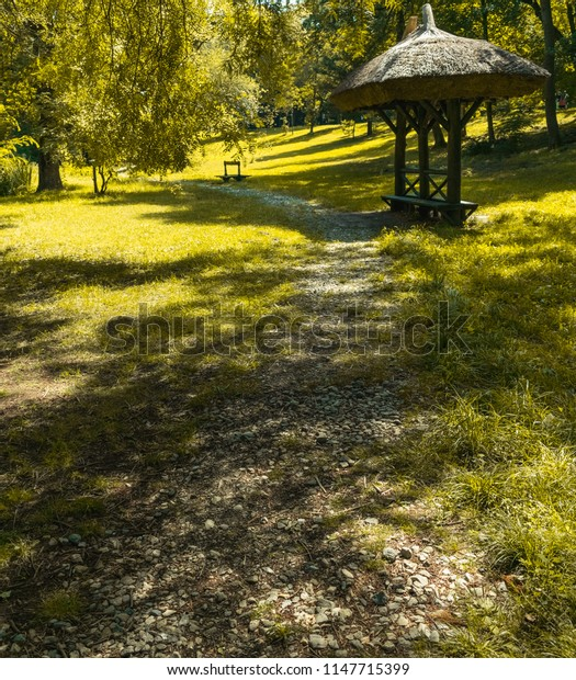 Trail towards a small bench cottage situated in a natural park, Craiova, Romania