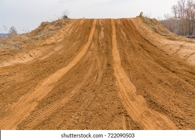 Trail of treads on a sandy quarry background.