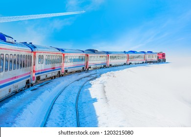 Trail of white smoke from the airplane - Red passenger diesel train moving at the terminal. Snow covered railway tracks - East express between Ankara and Kars - Turkey