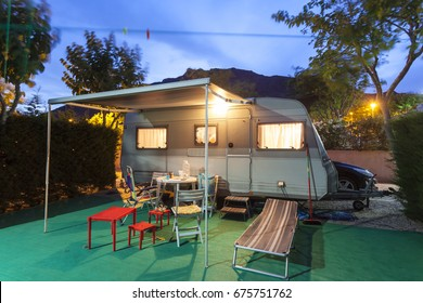 Trailer caravan on a camping site illuminated at night