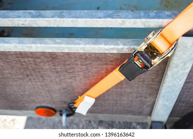 Trailer strop or strap in orange nylon and metal, object helping for holding stuff , storage and transport for safty and security.