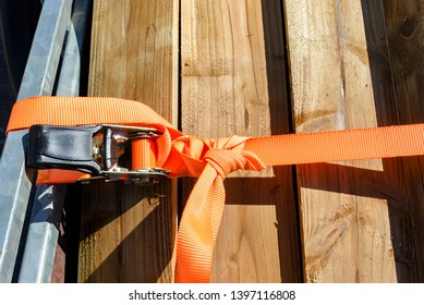 Trailer strop or strap in orange nylon and metal tie down with wood and trailer. Object helping for holding stuff , storage and transport for safty and security.