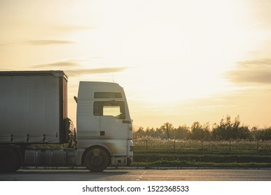 Trailer truck on a parking on sunset rays background.
