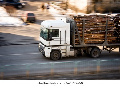 Trailer truck on speed. Trailer truck carries logs.