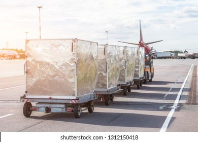 Trailers with containers of onboard aviation food for loading into a passenger airplane.