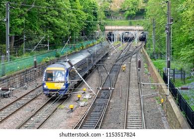 Train approaching Waverley station through Princes Street Gardens in Edinburgh, Scotland