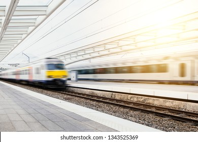 Train arrives at a white minimal station at sunset
