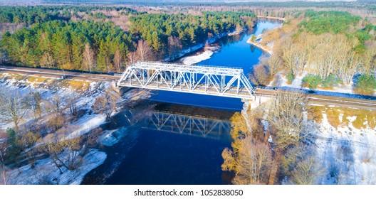 Train bridge across river aerial view. Small steel river bridge.