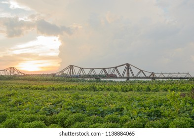 A train come across Long Bien bridge in beautiful sunset - a historic cantilever bridge across the Red River that connects two districts, Hoan Kiem and Long Bien of the city of Hanoi, Vietnam.