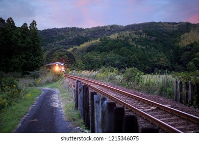 Train comes around bend in track under beautiful sunset sky in rural Japan