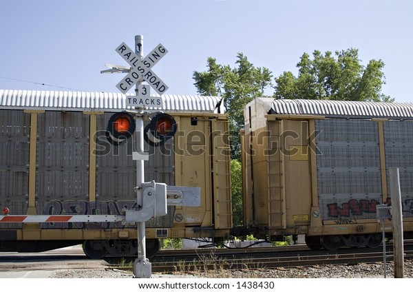 Train crossing - gates are down and lights are flashing - clear summer day.