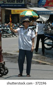 train crossing guard in her uniform directing street traffic in Hanoi, Vietnam