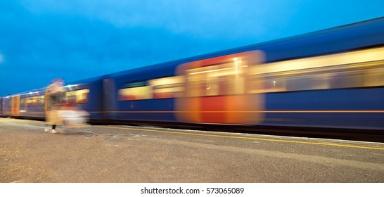 Train departing a UK station and gathering speed