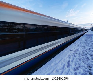 Train departing a UK station at speed in the snow