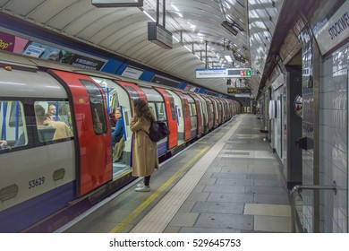 Train departing from an underground Tube Station on November 13, 2016 in London, England. A woman as tourist thinks to go inside or not.