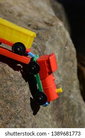 Train derailed, colourful plastic toy train with carriages, hanging over cliff. Concept of danger,  accident, travel, transportation, playful childhood.