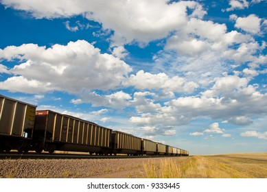 train disappearing into the distance under cloudy blue sky