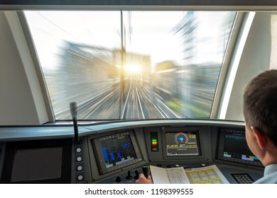 Train driver at the controls cab of speed passenger train, view of the railway bridge with the effect of speed motion blur