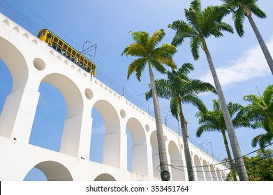 Train drives along distinctive white arches of the landmark Lapa Arches in Rio de Janeiro, Brazil
