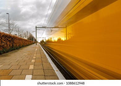 Train of the Dutch railways passes the platform of a train station in Delft at high speed
