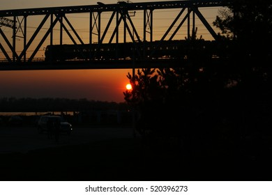 the train goes over the bridge at sunset
