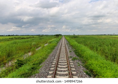 Train going fast over track through green contryside